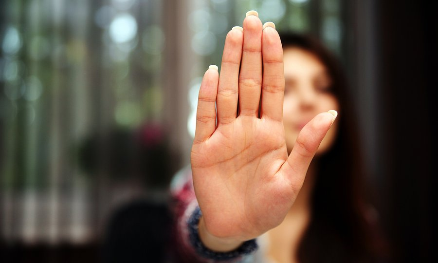 Woman with her hand extended signaling to stop (only her hand is