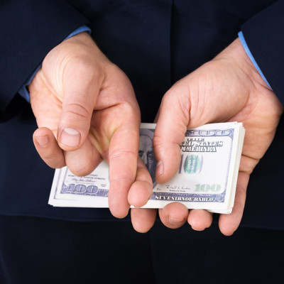 Businessman With Finger Crossed Holding Banknotes